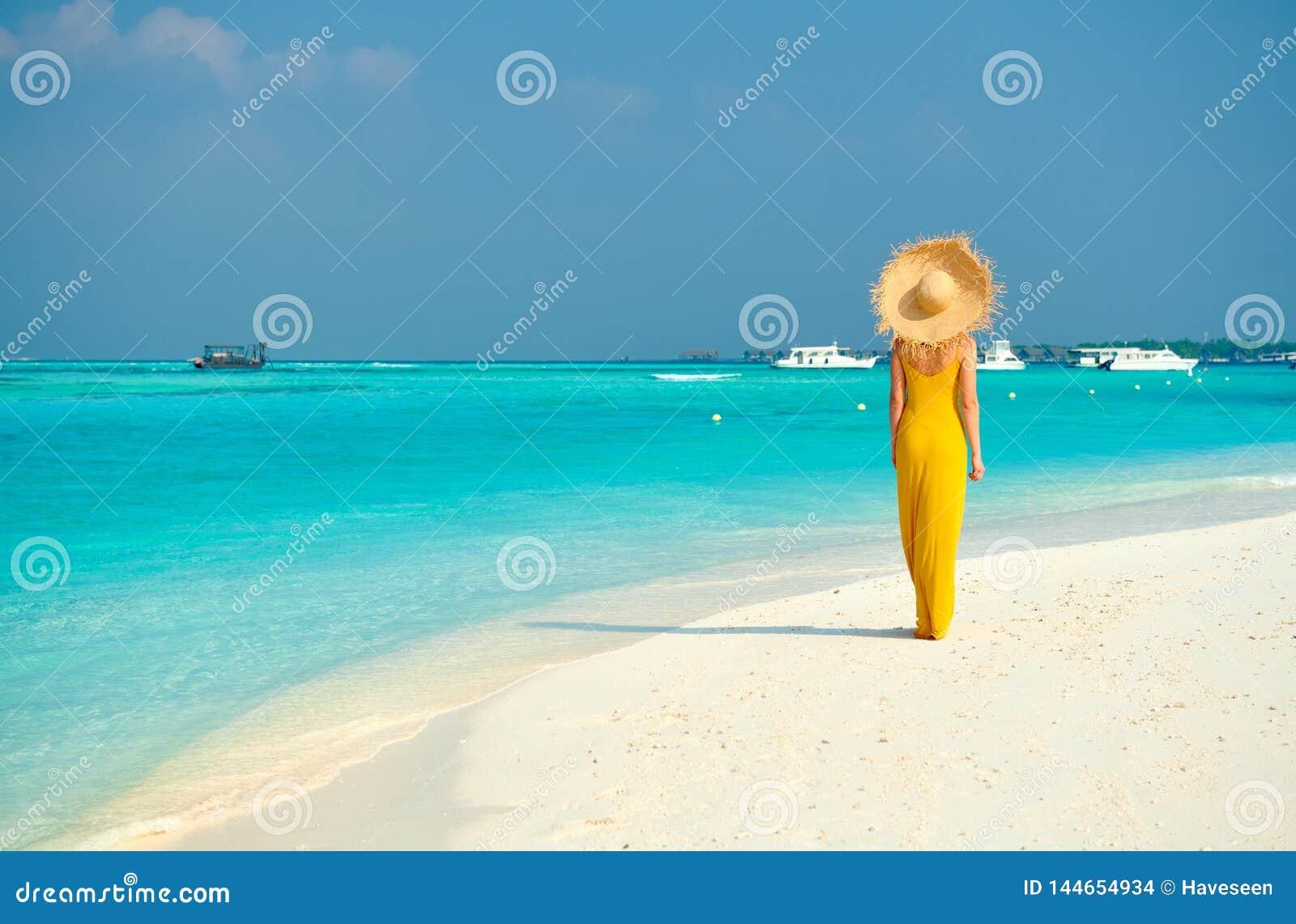 Donna in vestito che cammina sulla spiaggia tropicale