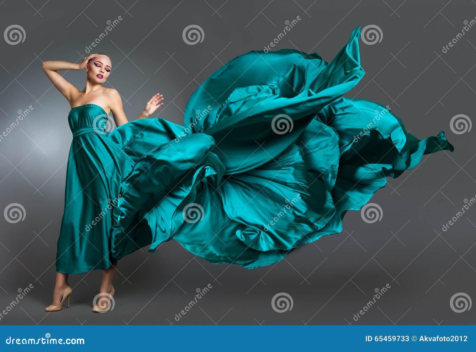 Donna in vestito di seta che ondeggia sul vento Panno volante e d ondeggiamento dell abito sopra fondo grigio