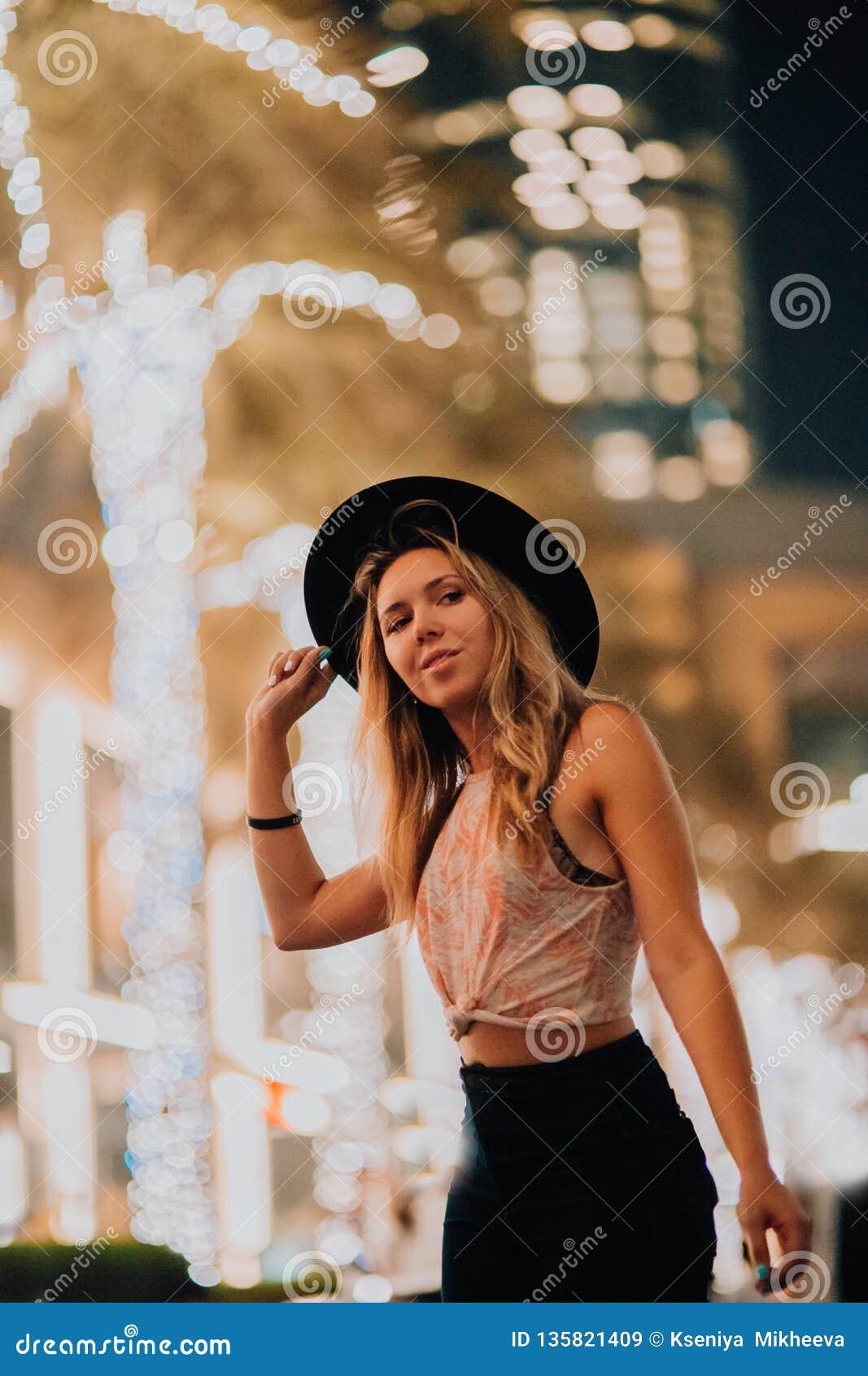 Donne belle in vestiti alla moda del cappello, uomo brutale, attrezzatura alla moda, passeggiata giù la via luce e palme fresche