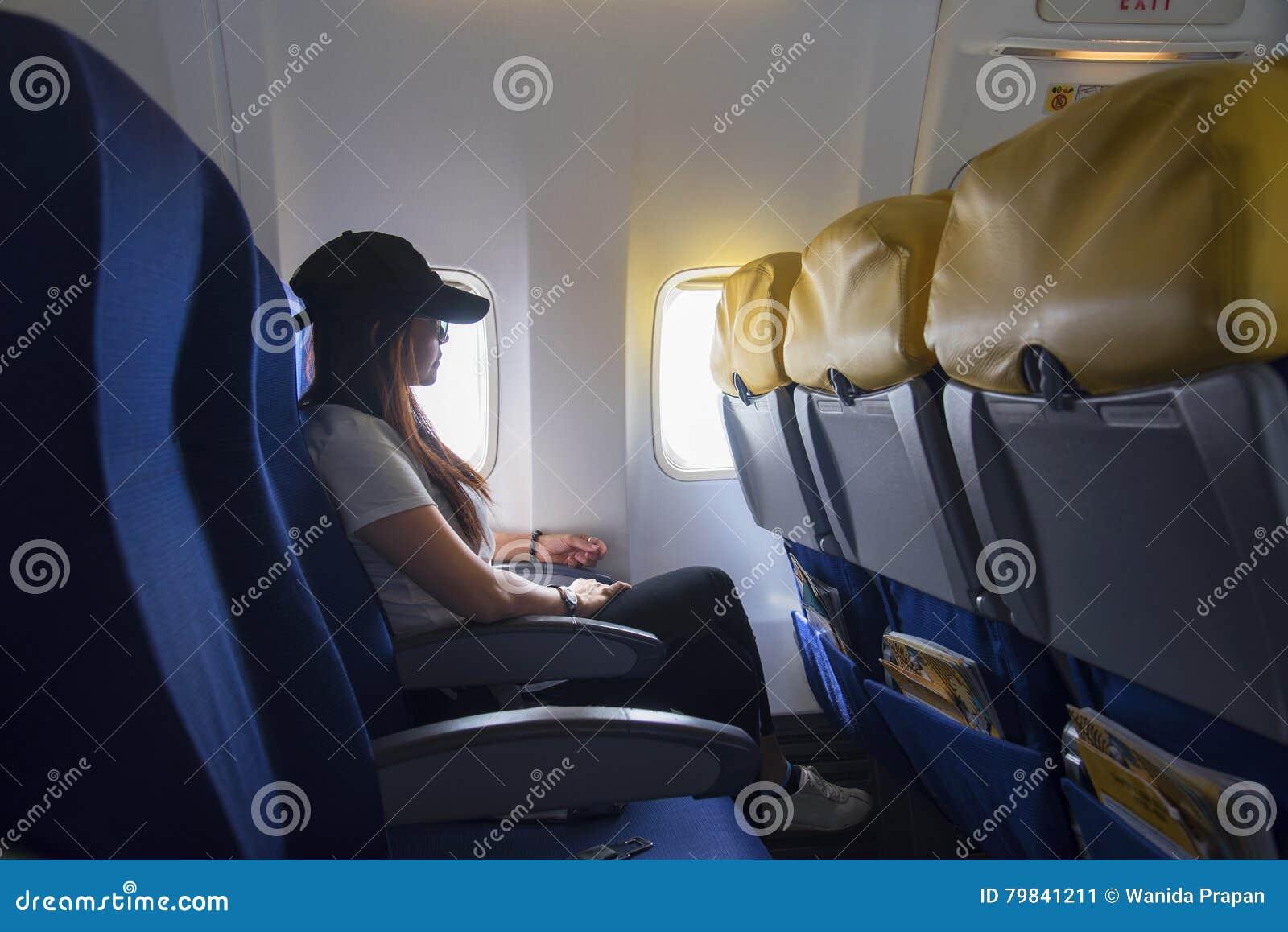 Donne che viaggiano in aeroplano Donne che si siedono dalla finestra degli aerei e che guardano fuori