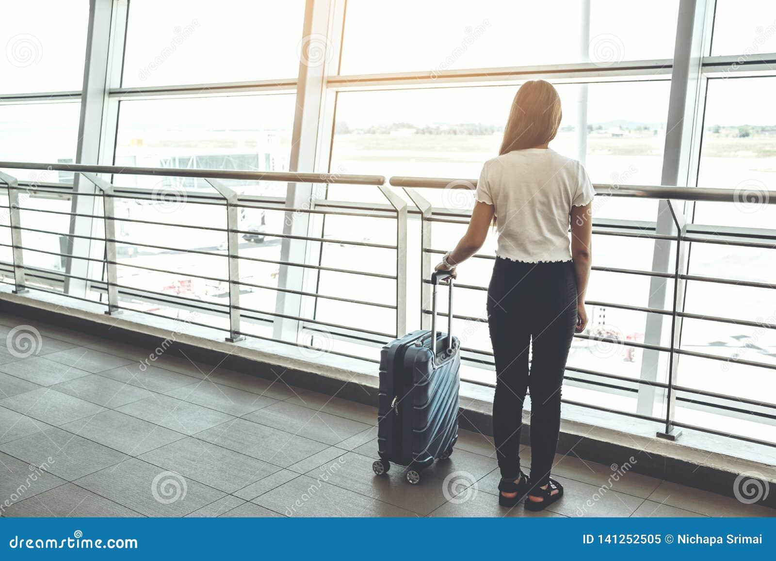 Donne e bagagli del viaggiatore al concetto di viaggio del terminale di aeroporto