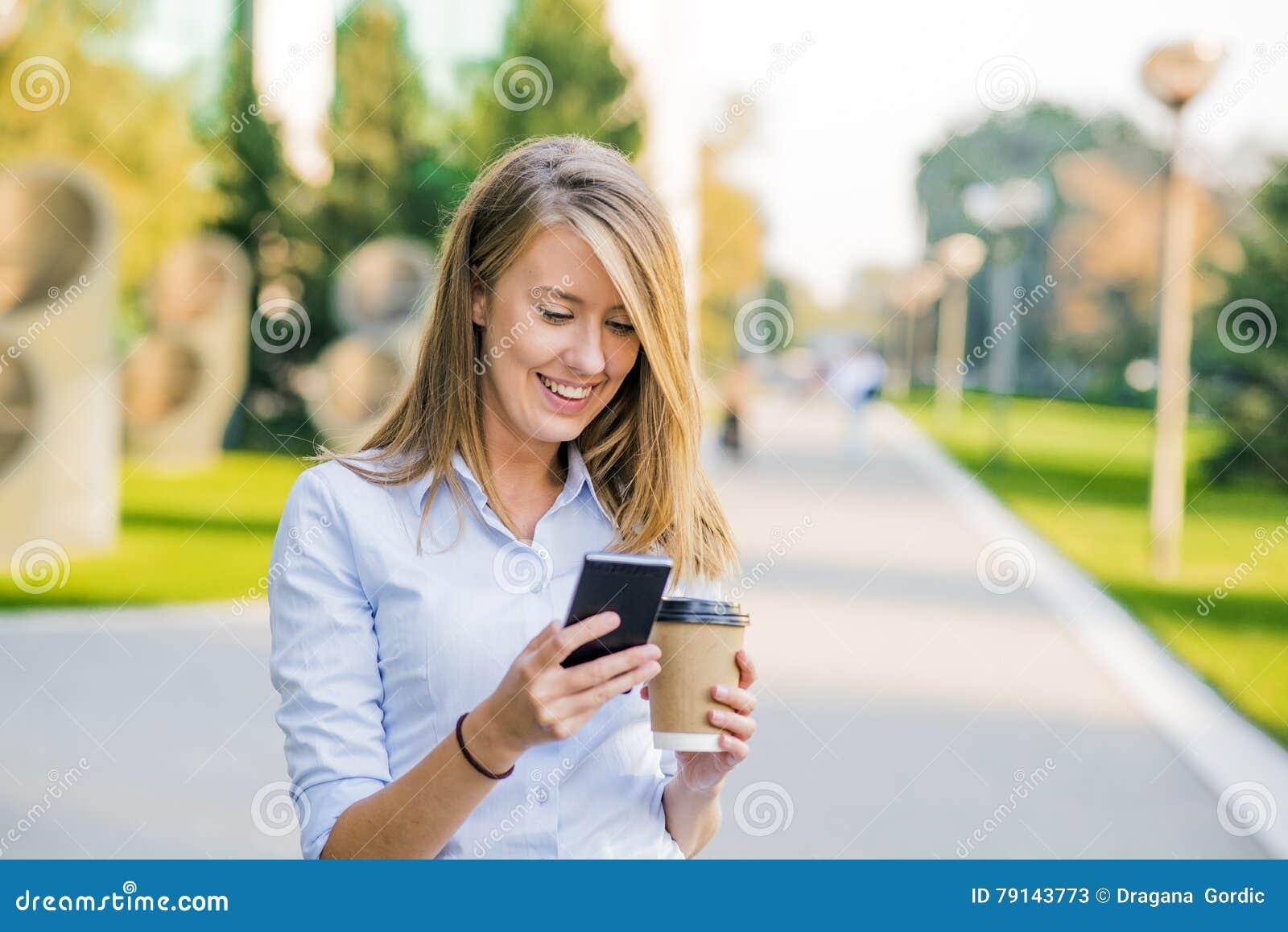 Donne sicure che leggono informazioni sulle notizie di finanza mentre camminando nel corridoio della società durante la pausa di