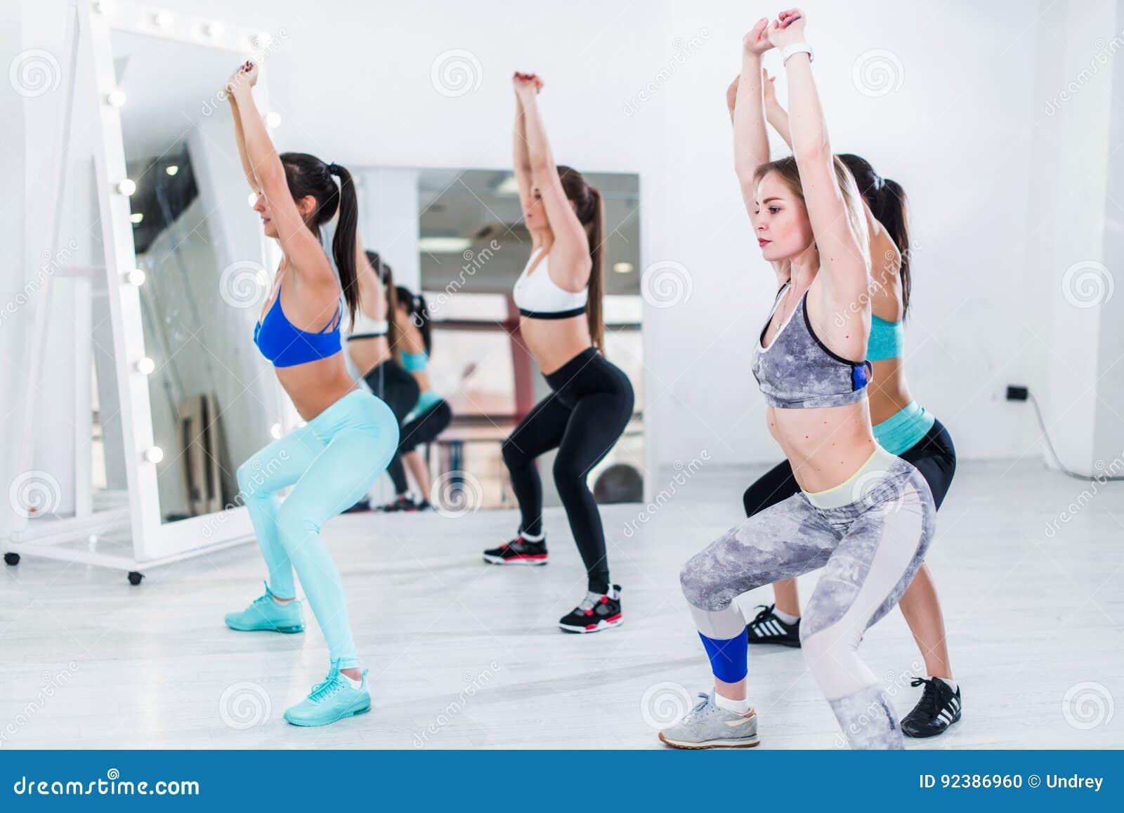 Donne snelle giovani che fanno esercizio tozzo di spese generali durante l addestramento del gruppo nella palestra