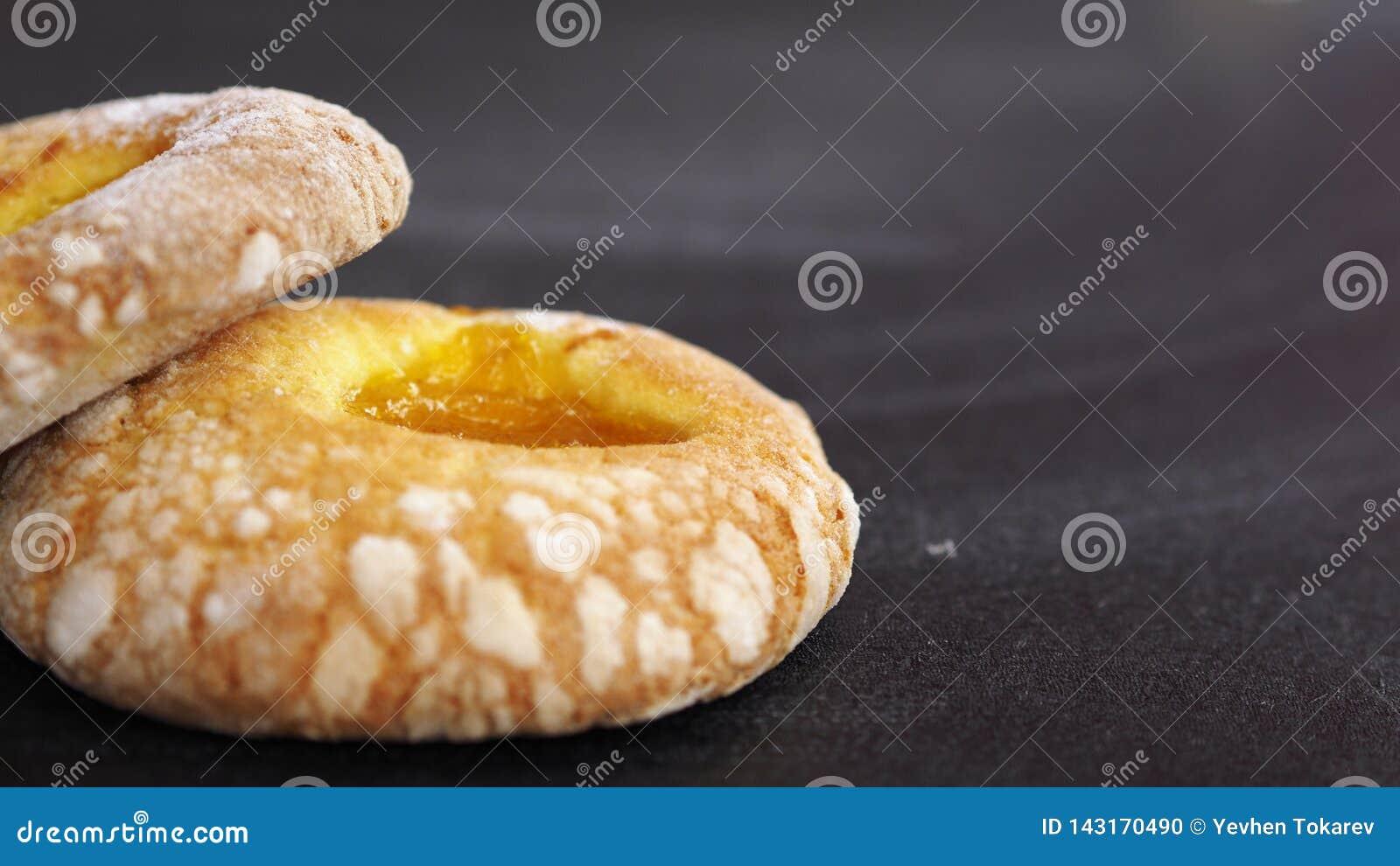 2 donuts с вареньем абрикоса на левой стороне черная предпосылка