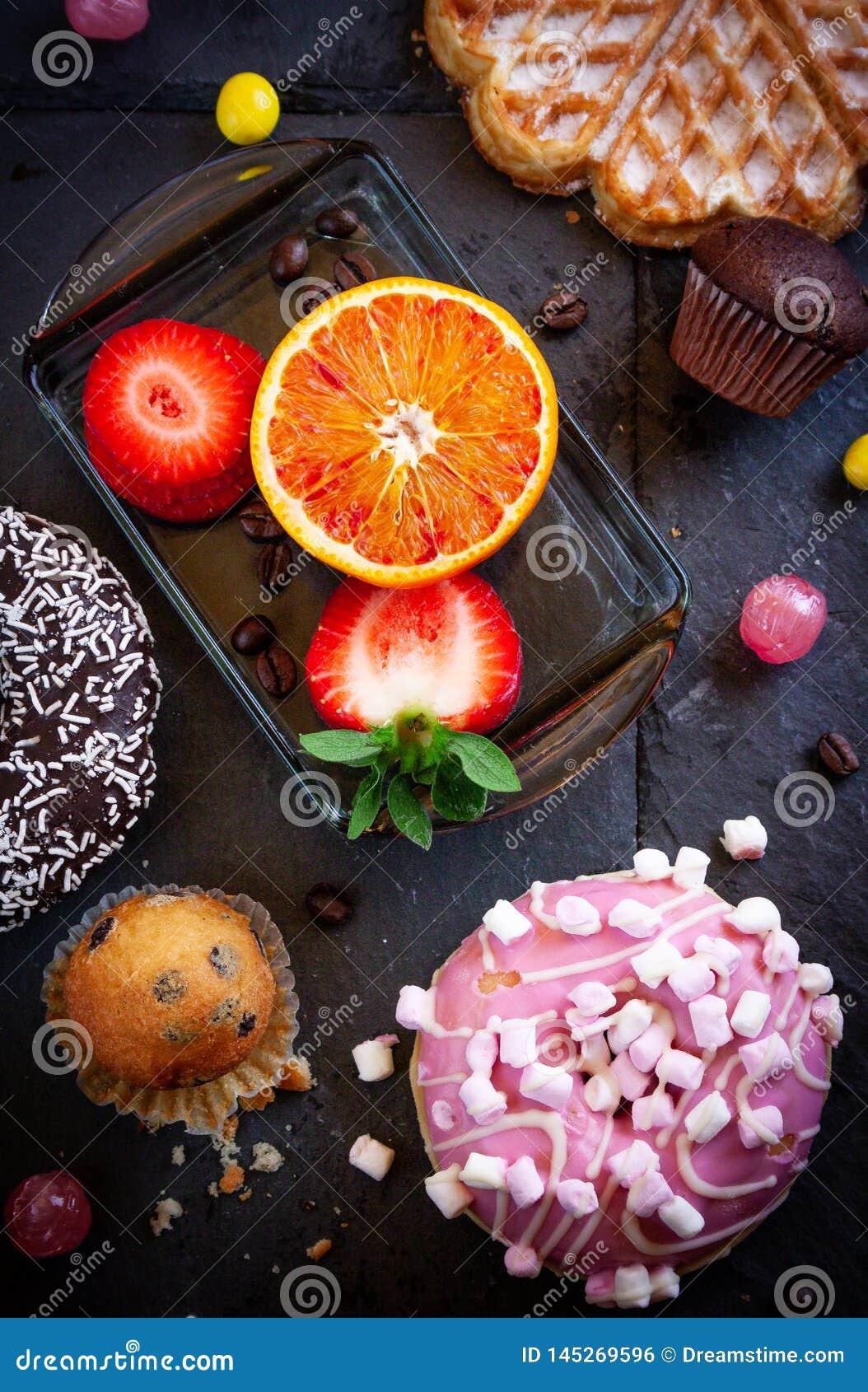 Donuts en muffins met fruit op zwarte steenachtergrond