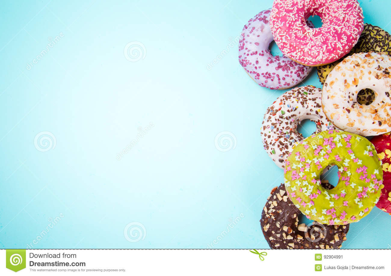 Donuts Glazed With Sprinkles On Pastel Blue Background