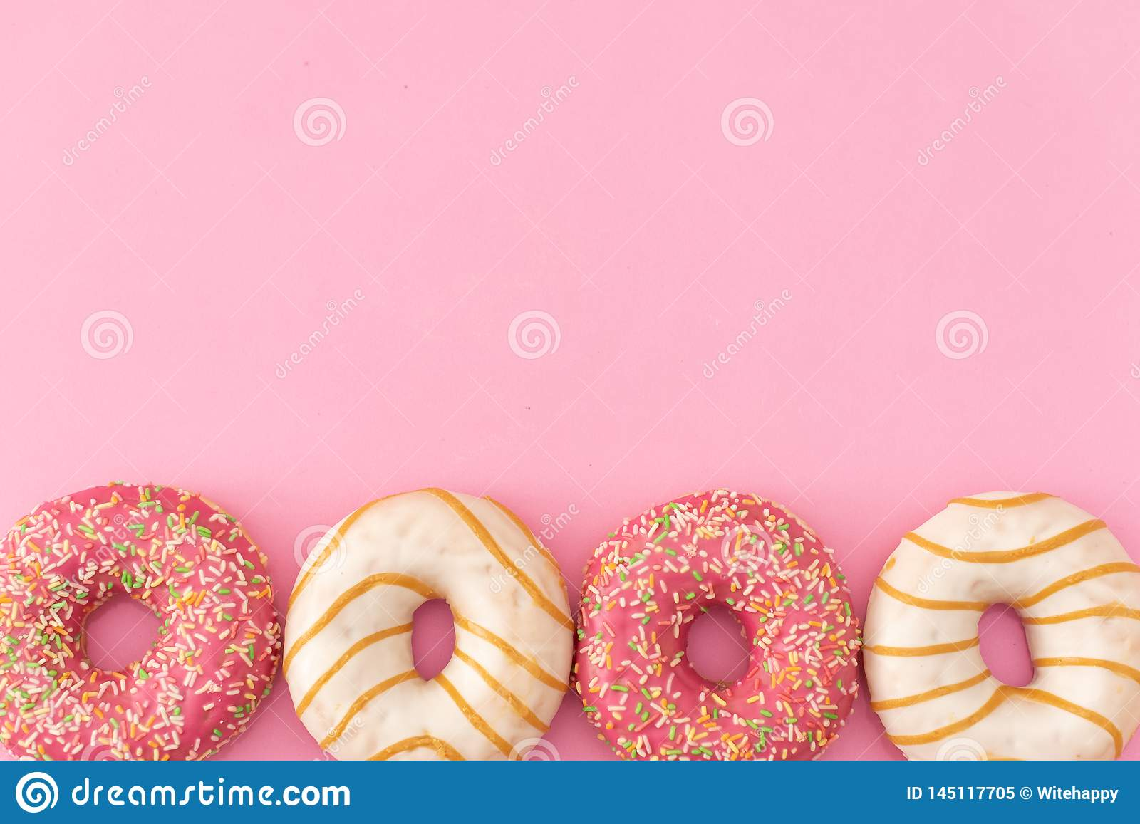 Donuts with icing on pastel pink background. Sweet donuts