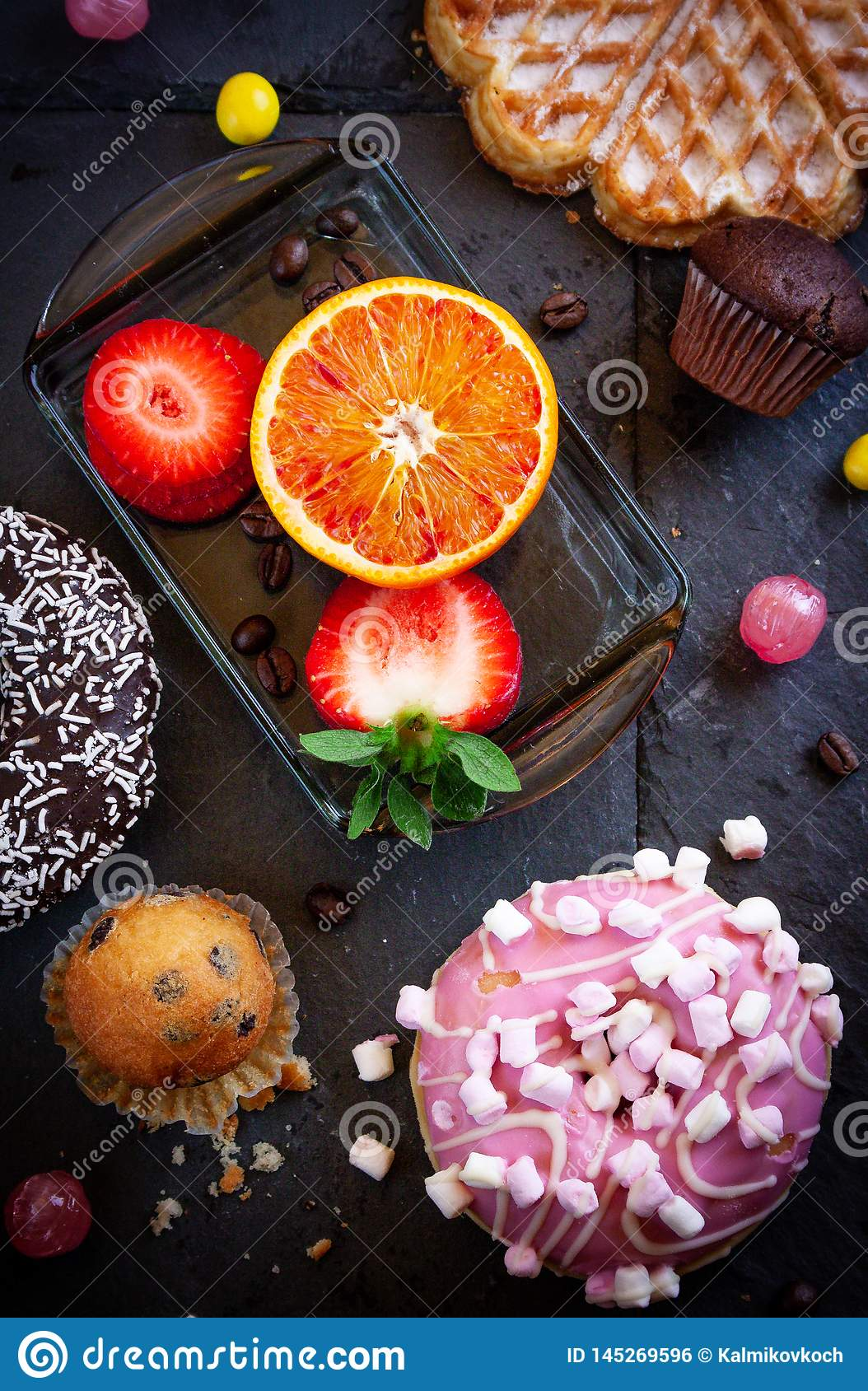Donuts and muffins with fruit on black stone background.