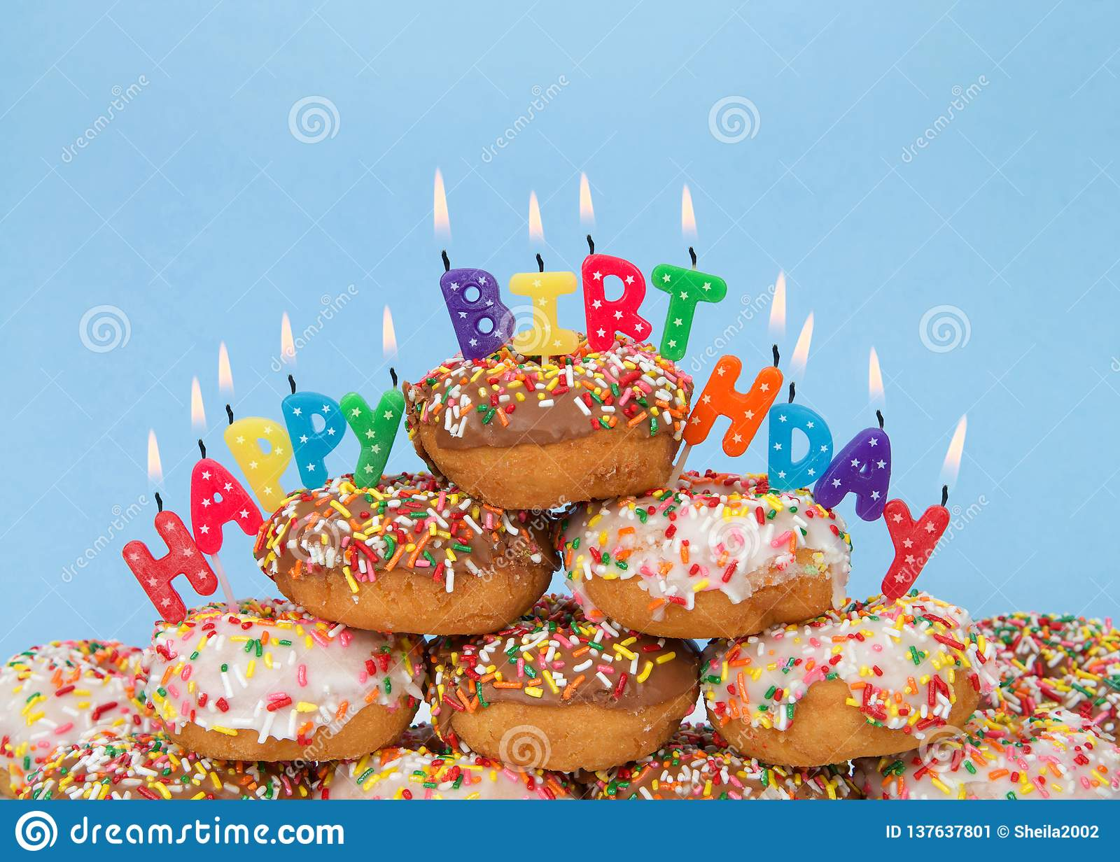 donuts stacked with happy birthday candles blue
