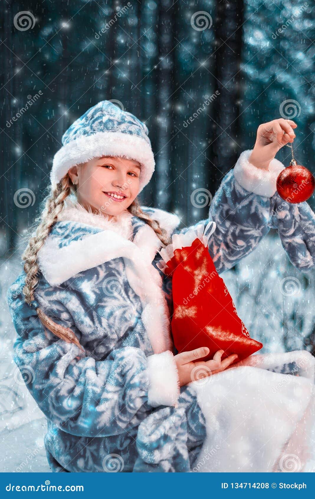Donzela alegre no traje festivo a menina é de sorriso e guardando um brinquedo e um saco de ano novo com presentes floresta do in