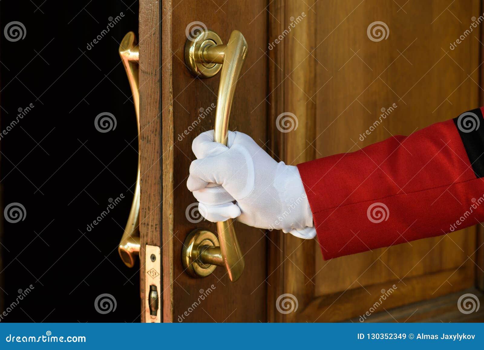 The doorman opens the hotel door hands in white gloves