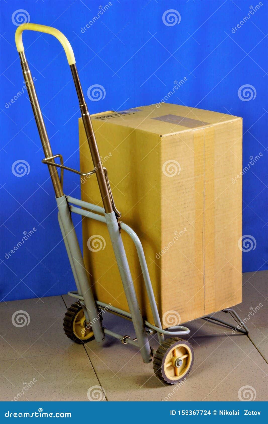 Doos op een kar, levering van goederen en pakketten De doos of de kartondoos worden op een hand vervoerd die kar vouwen - het bes