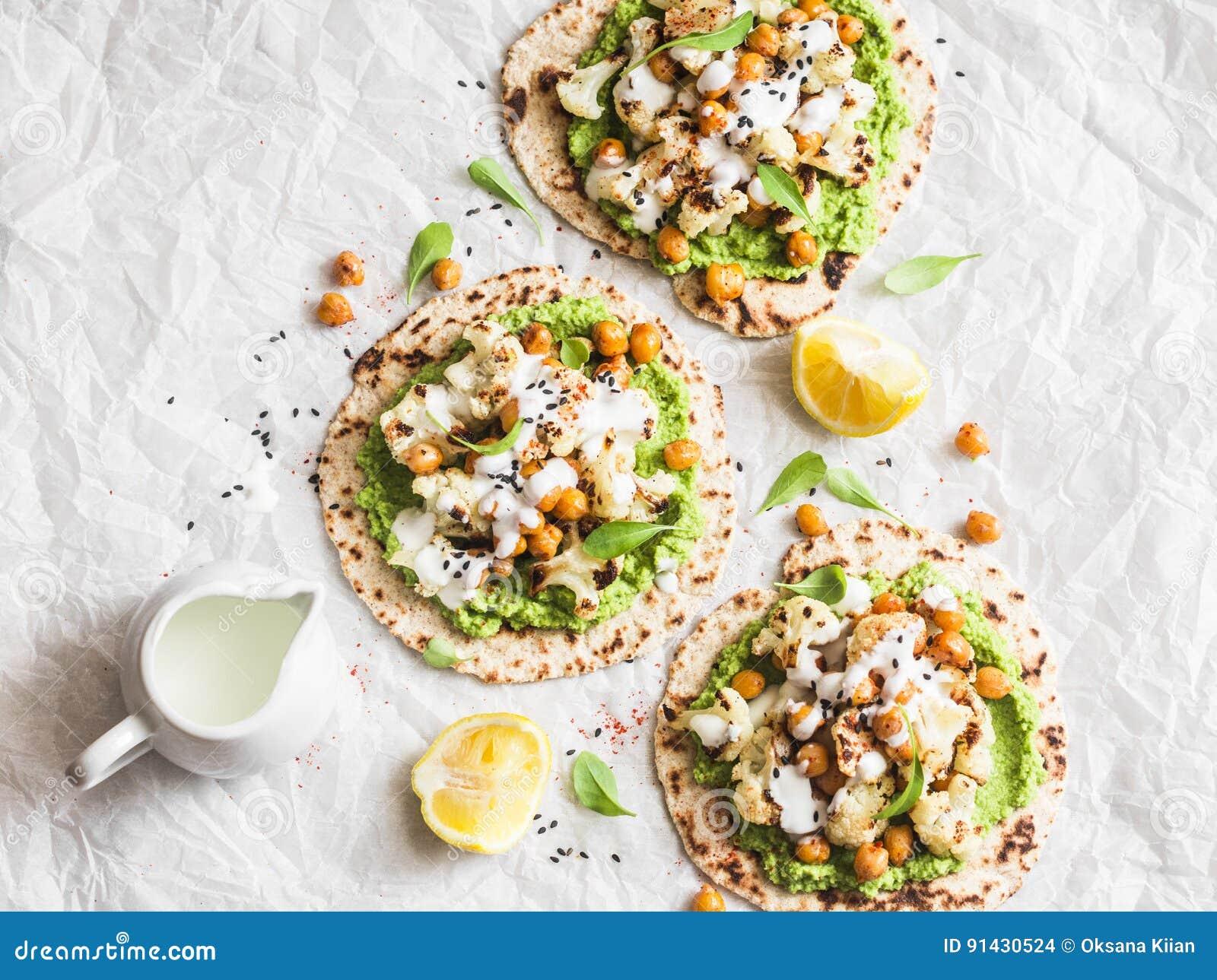 Doppar fri tunnbröd för gluten med grillade kikärtar, blomkålen och avokadot på en ljus bakgrund, bästa sikt sund vegetarian för
