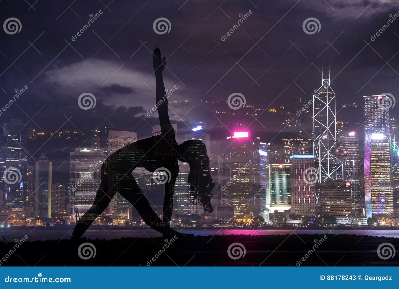 Doppelbelichtung der Schattenbildyogafrau gegen Hong Kong-Stadt