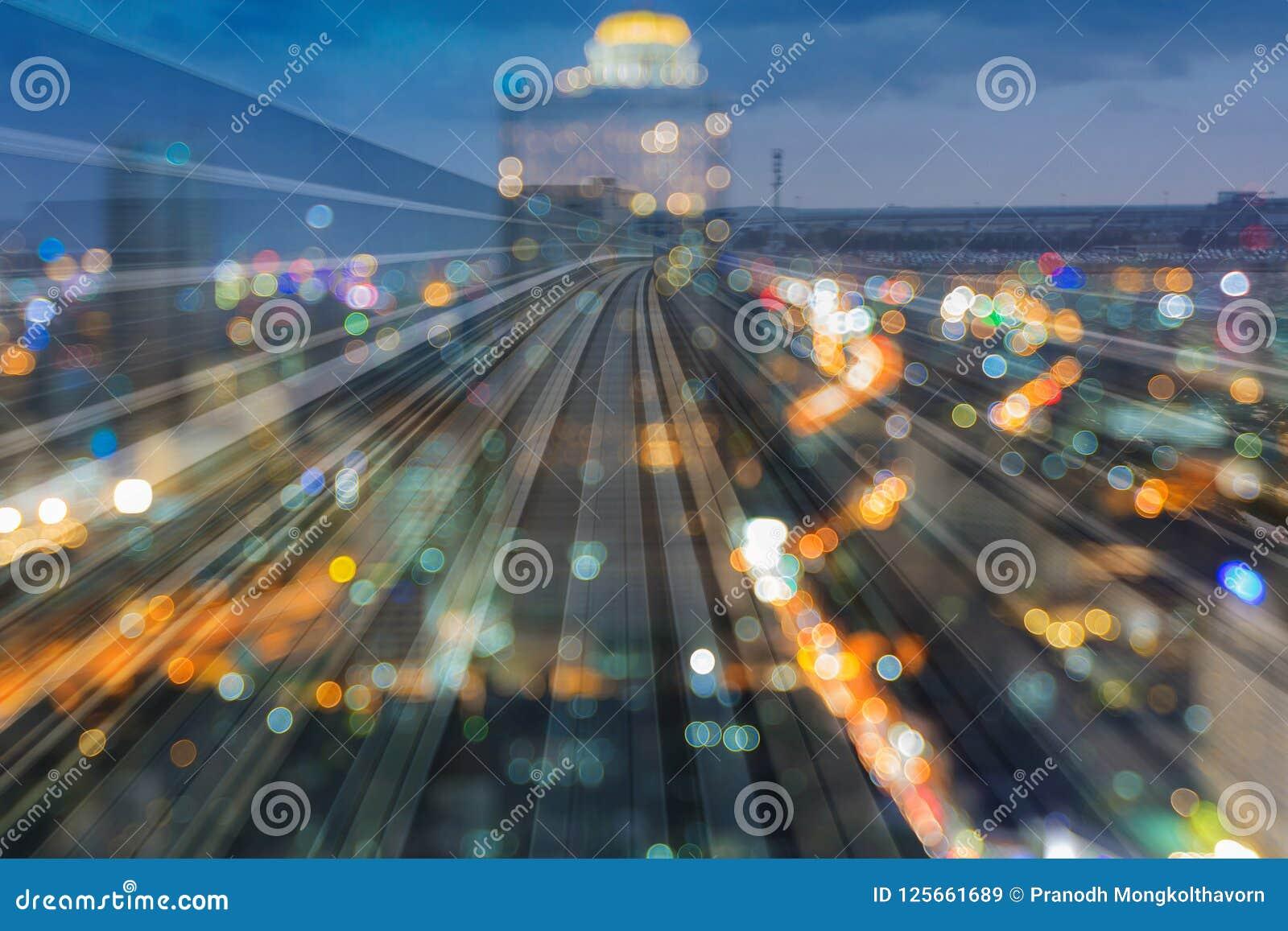 Doppeltexposé-Bahngleisbewegung des Dämmerungsstadtunschärfelichtes in die Stadt