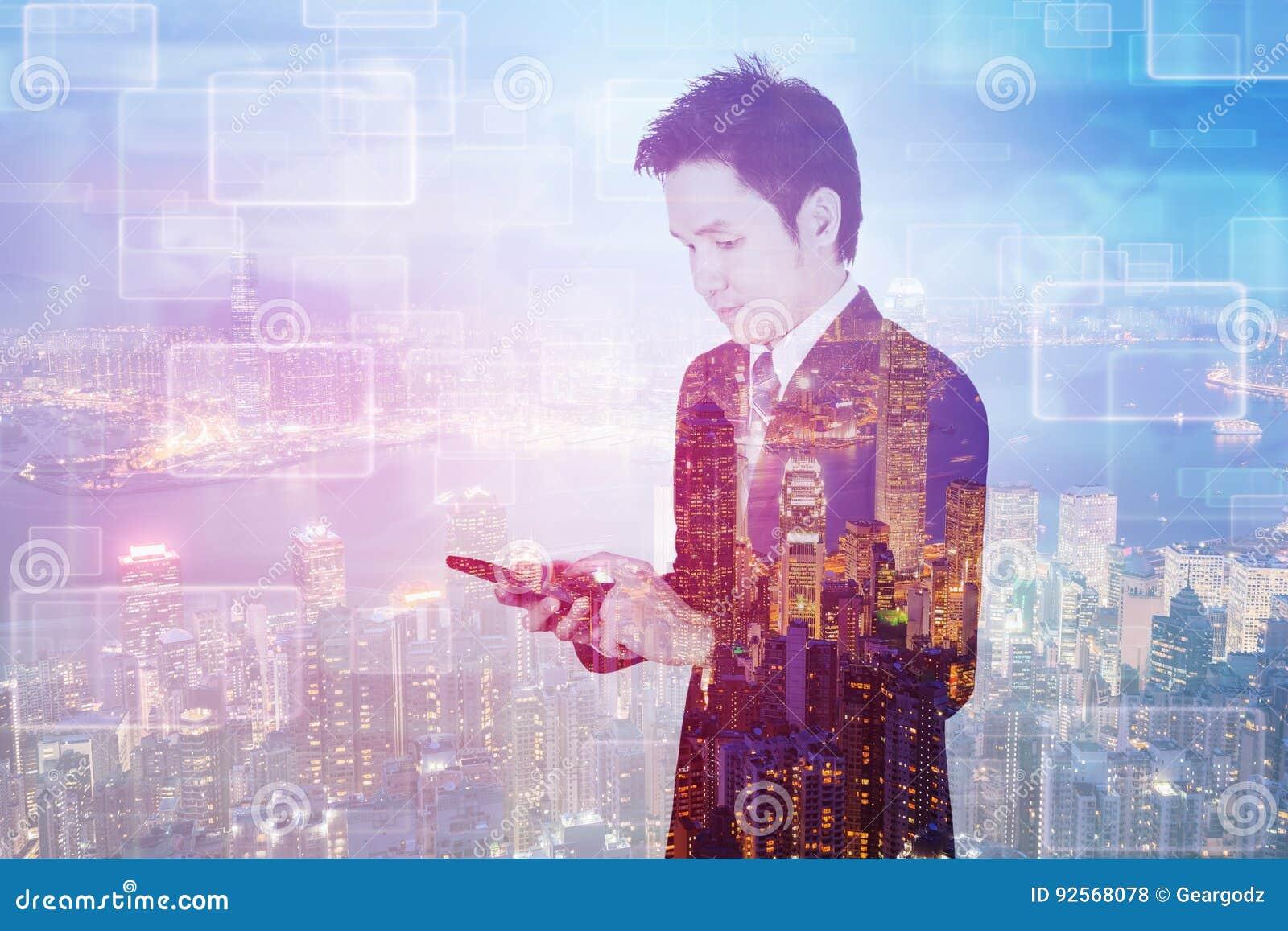 Doppia esposizione dell uomo di affari che per mezzo dello Smart Phone con la parte posteriore della città