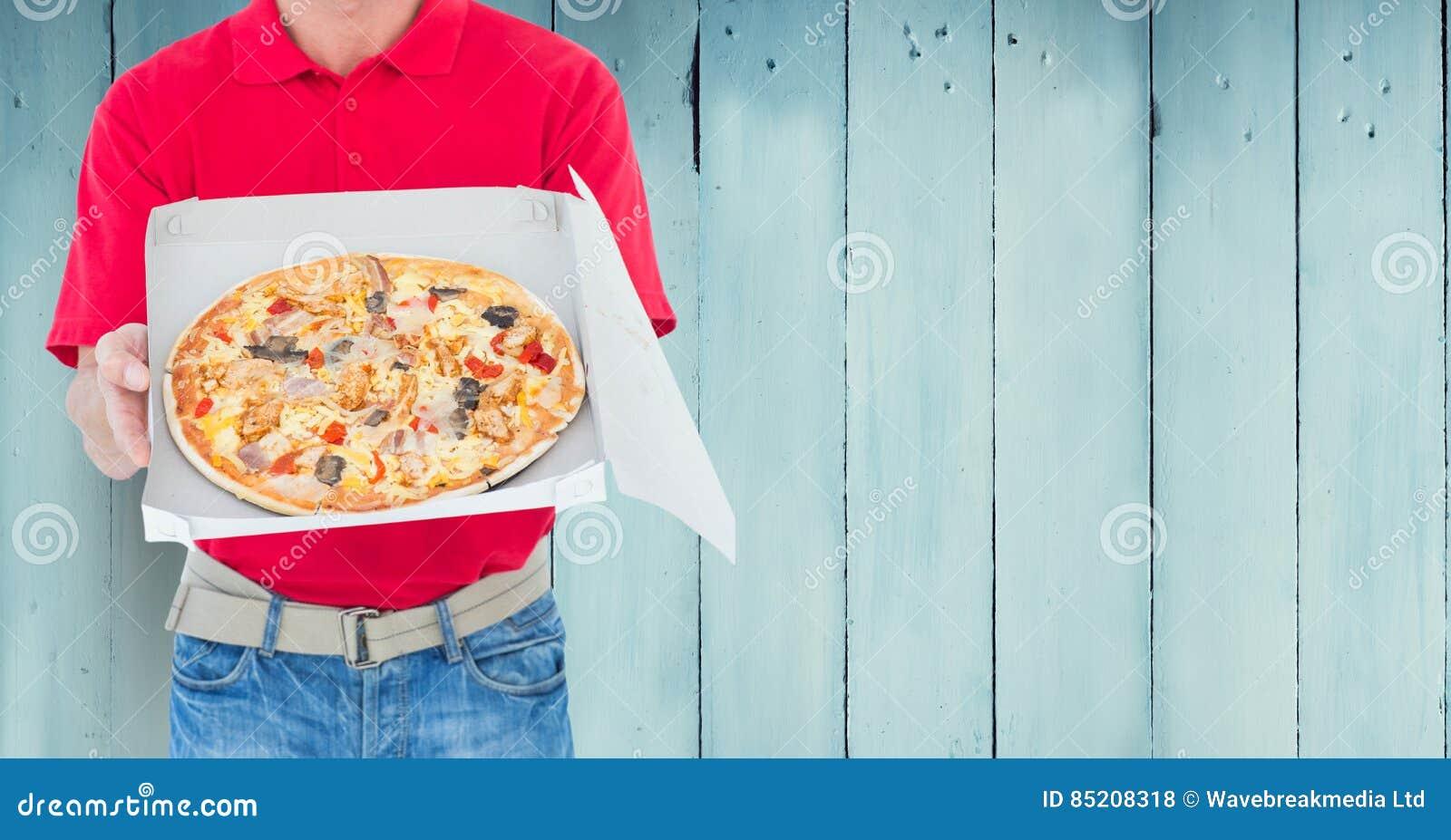 Doręczeniowego mężczyzna mienia pizzy pudełko przeciw drewnianemu tłu