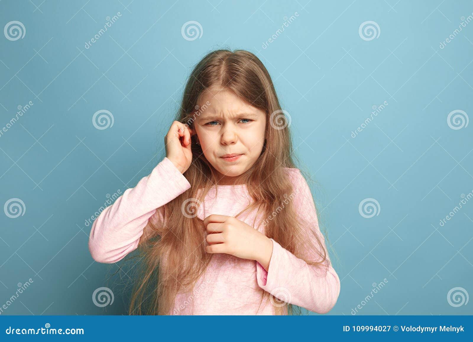 A dor da orelha Menina adolescente em um fundo azul Expressões faciais e conceito das emoções dos povos