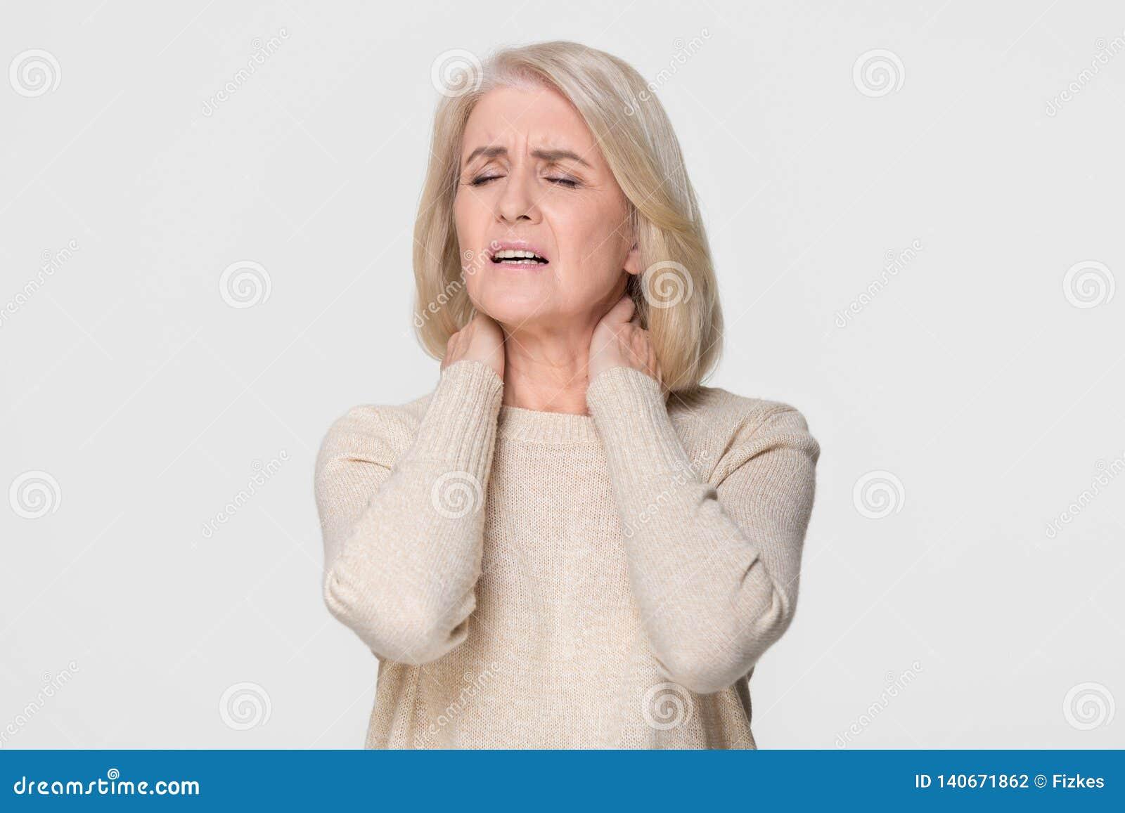 Dor de pescoço madura virada do sentimento da massagem da mulher isolada no fundo