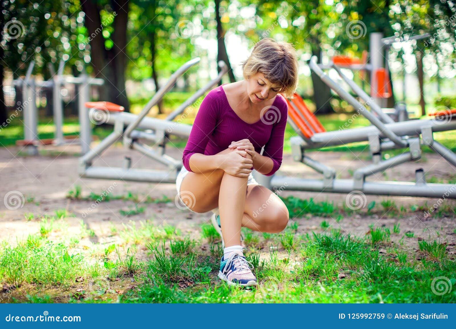 Dor do sentimento da jovem mulher em seu joelho durante o exercício do esporte no