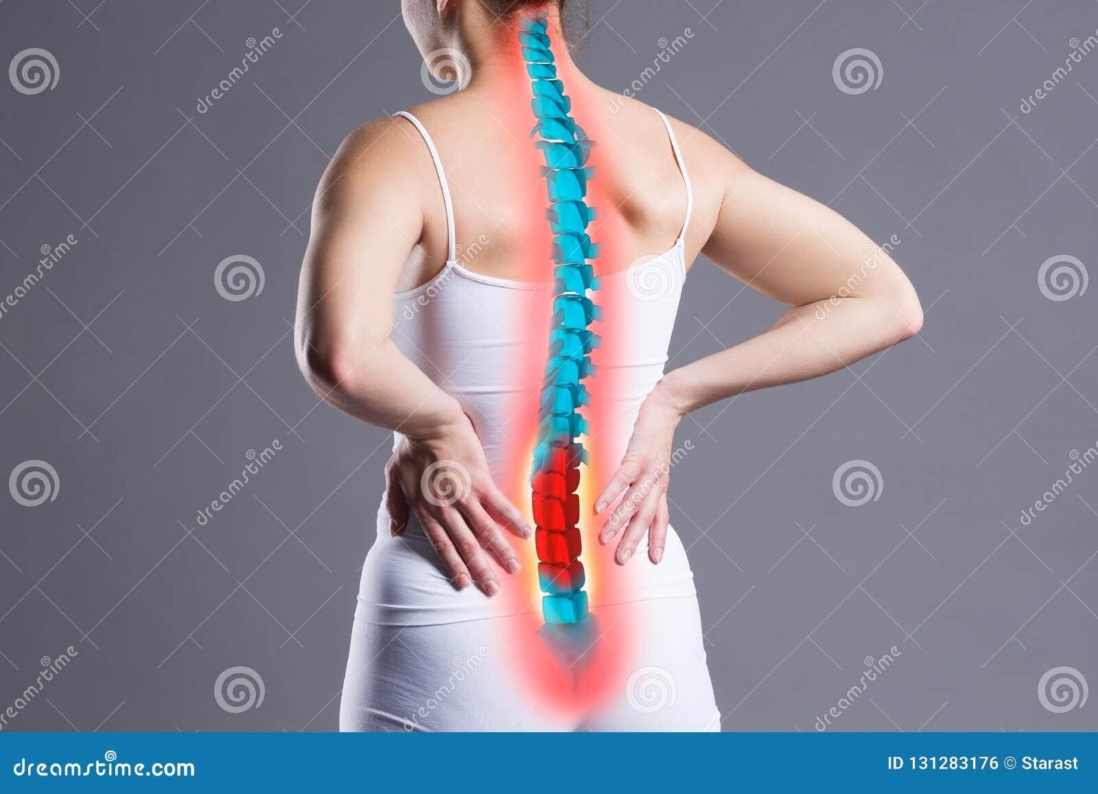 Dor na espinha, mulher com dor lombar no fundo cinzento, lesão dorsal
