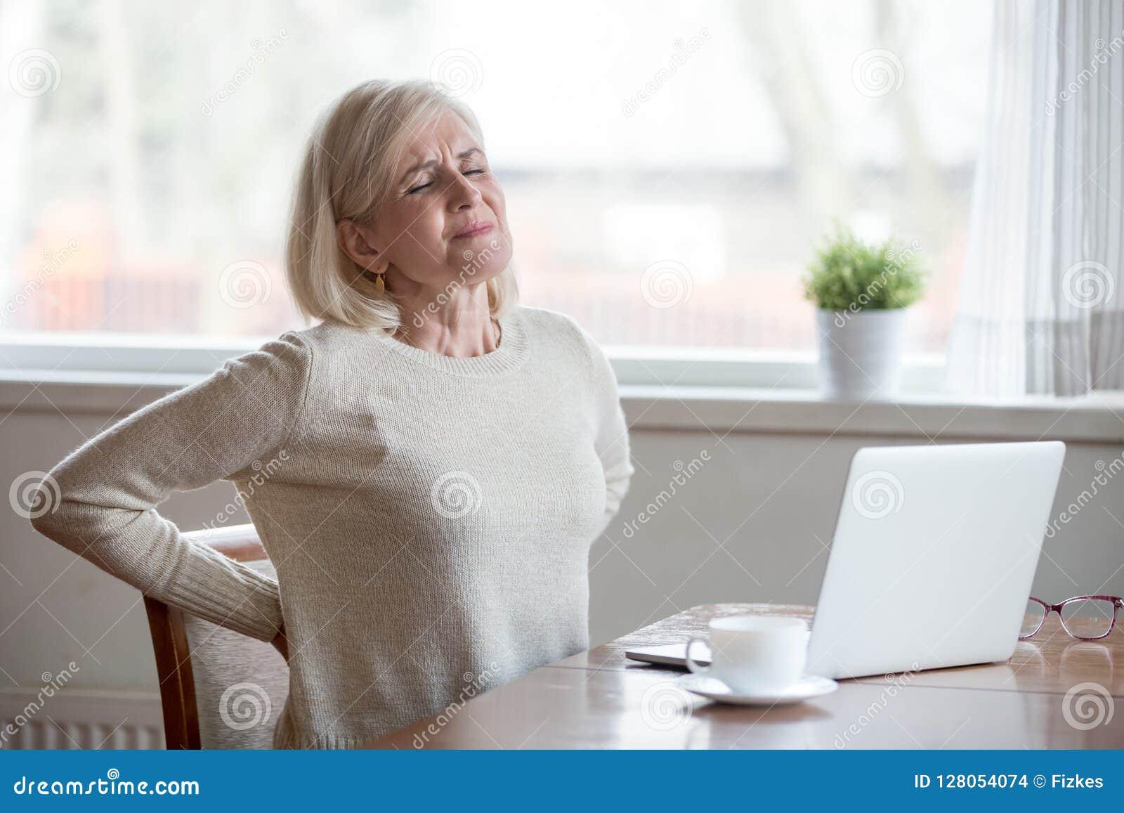 Dor nas costas de assento do sentimento da mulher madura virada que faz massagens a MU de dor