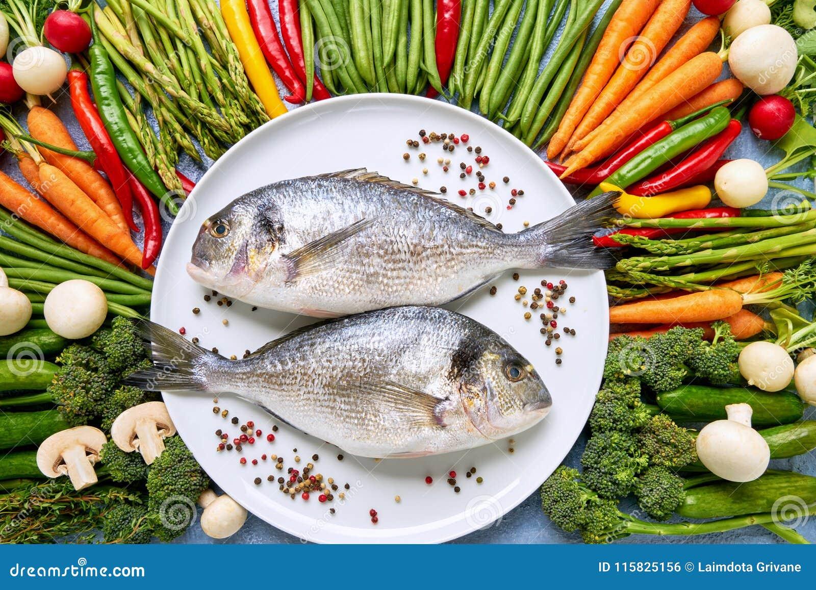 Doradavissen op witte schotel met kleurrijke rond groenten Dorad