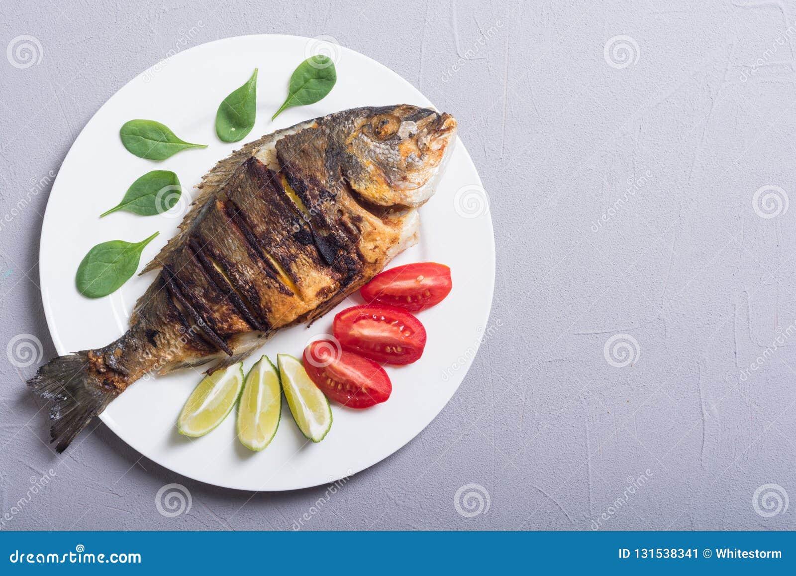 Dorado frito de los pescados con la cal, los tomates y la espinaca Alimento de mar