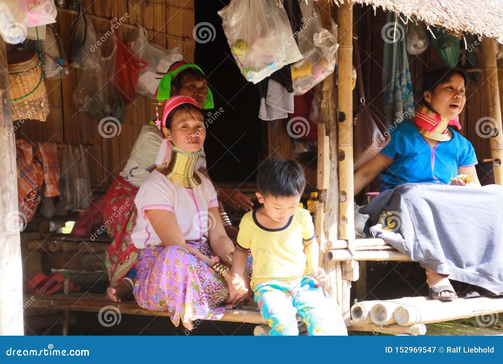 DORF LONGNECK KAREN, THAILAND - 17. DEZEMBER 2017: Lange Halsfamilie, die vor einer Bambushütte sitzt