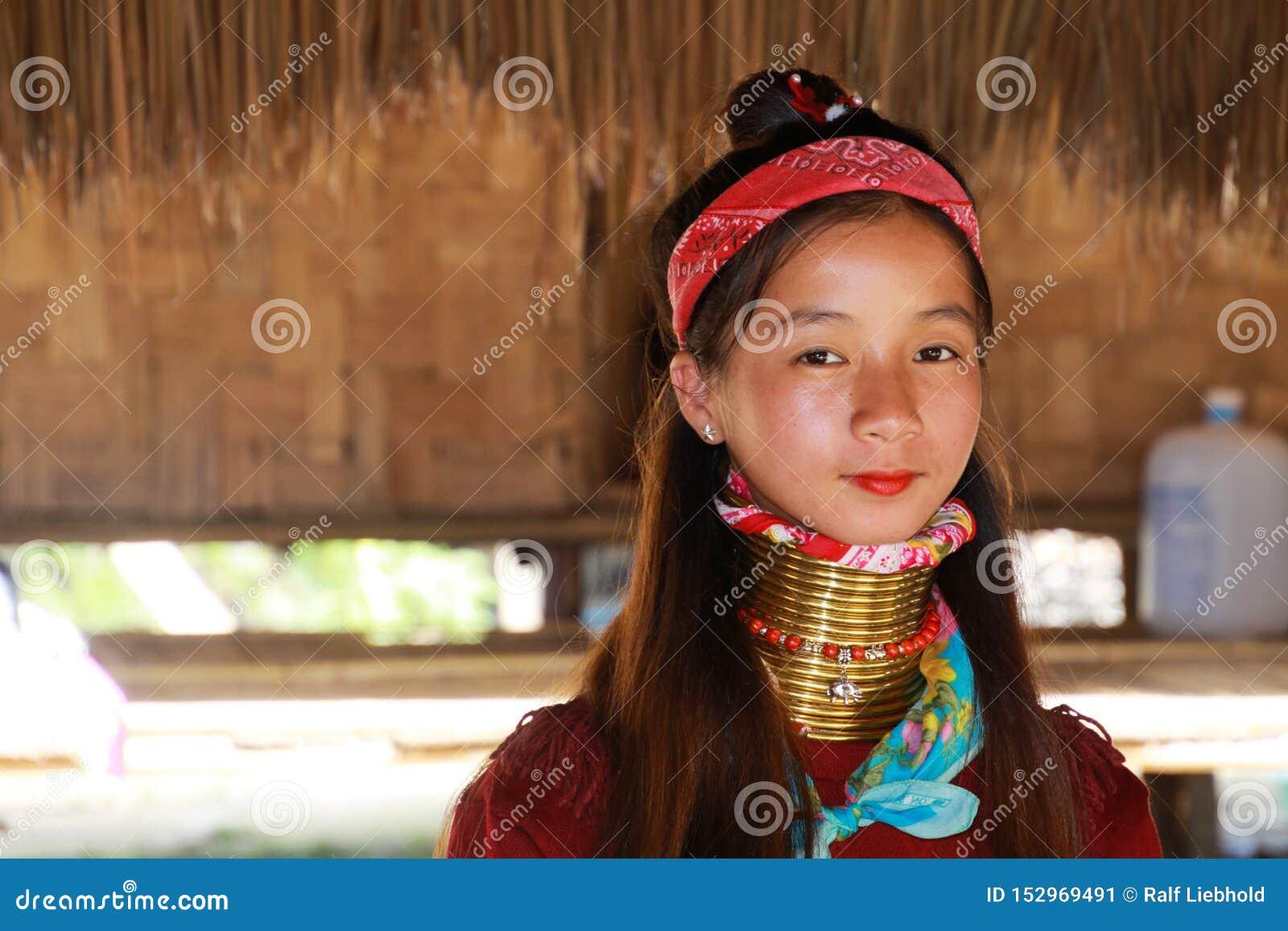 DORF LONGNECK KAREN, THAILAND - 17. DEZEMBER 2017: Nahes hohes Porträt des jungen langen Halsmädchens mit Thanaka-Gesichtsmalerei