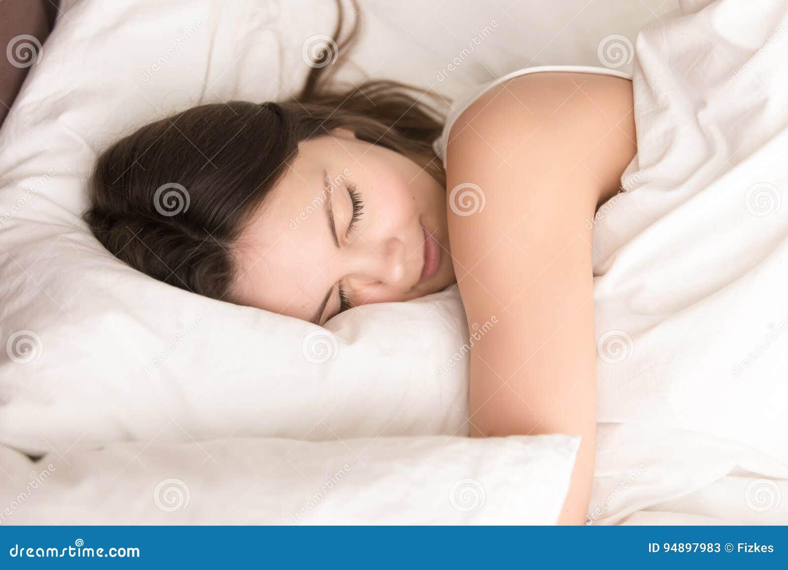 Dormida da mulher ao abraçar o descanso macio na cama