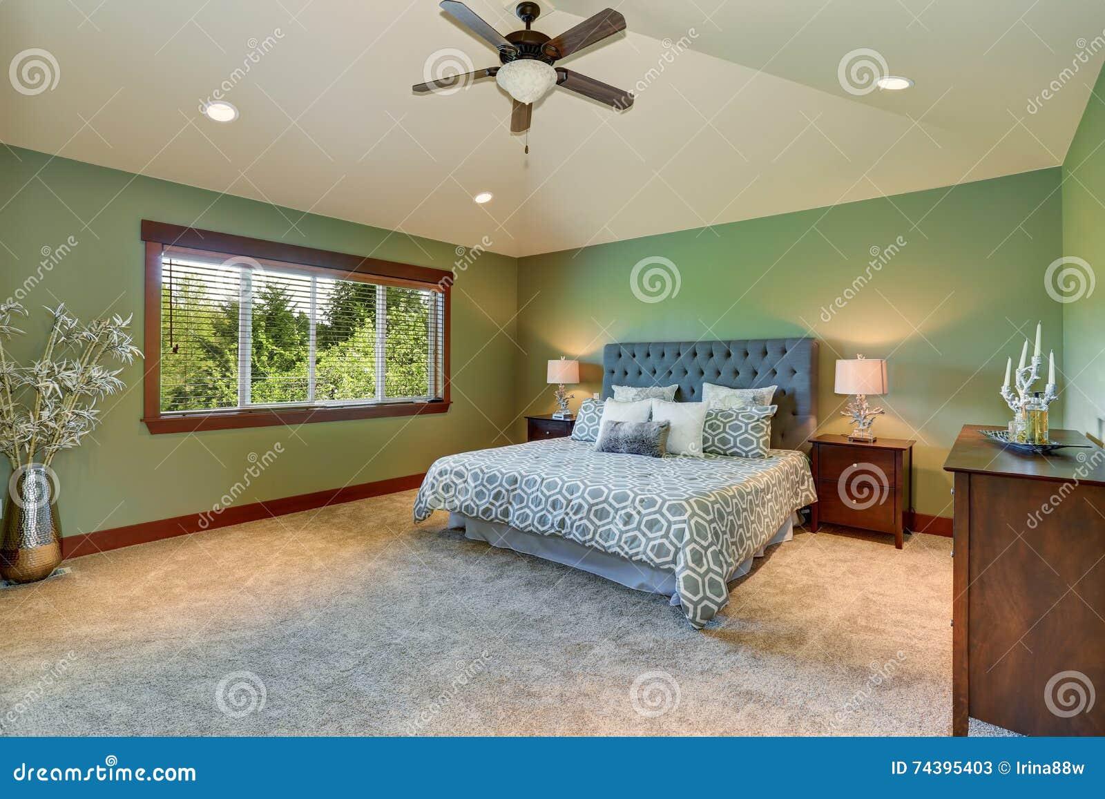 Dormitorio acogedor con la cama azul, el cabecero de los botones y las paredes verdes