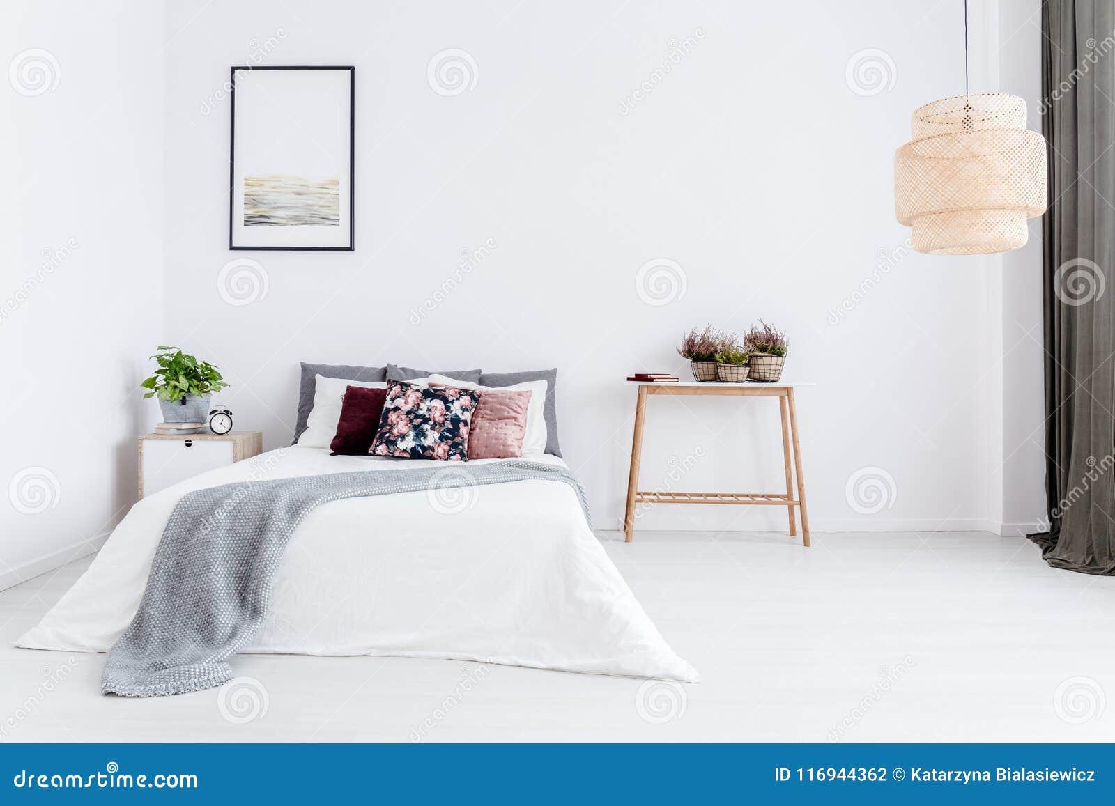 Dormitorio blanco con el amortiguador floral