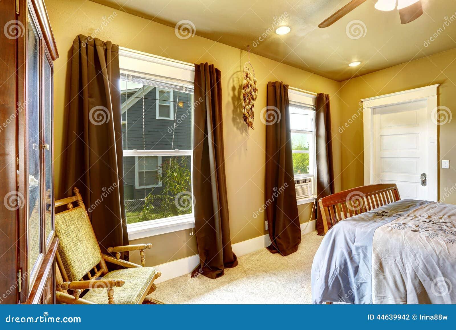 dormitorio caliente de los tonos con las cortinas marrones