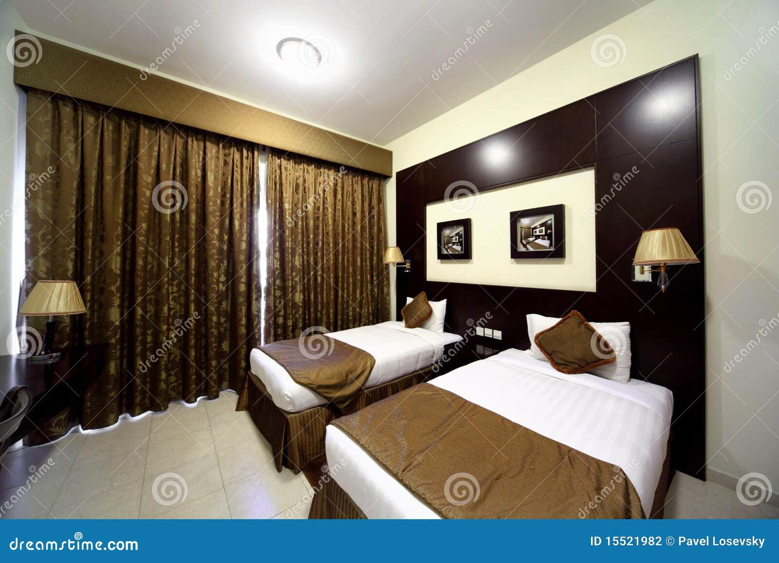Dormitorio con la cortina marrón cerrada y dos camas