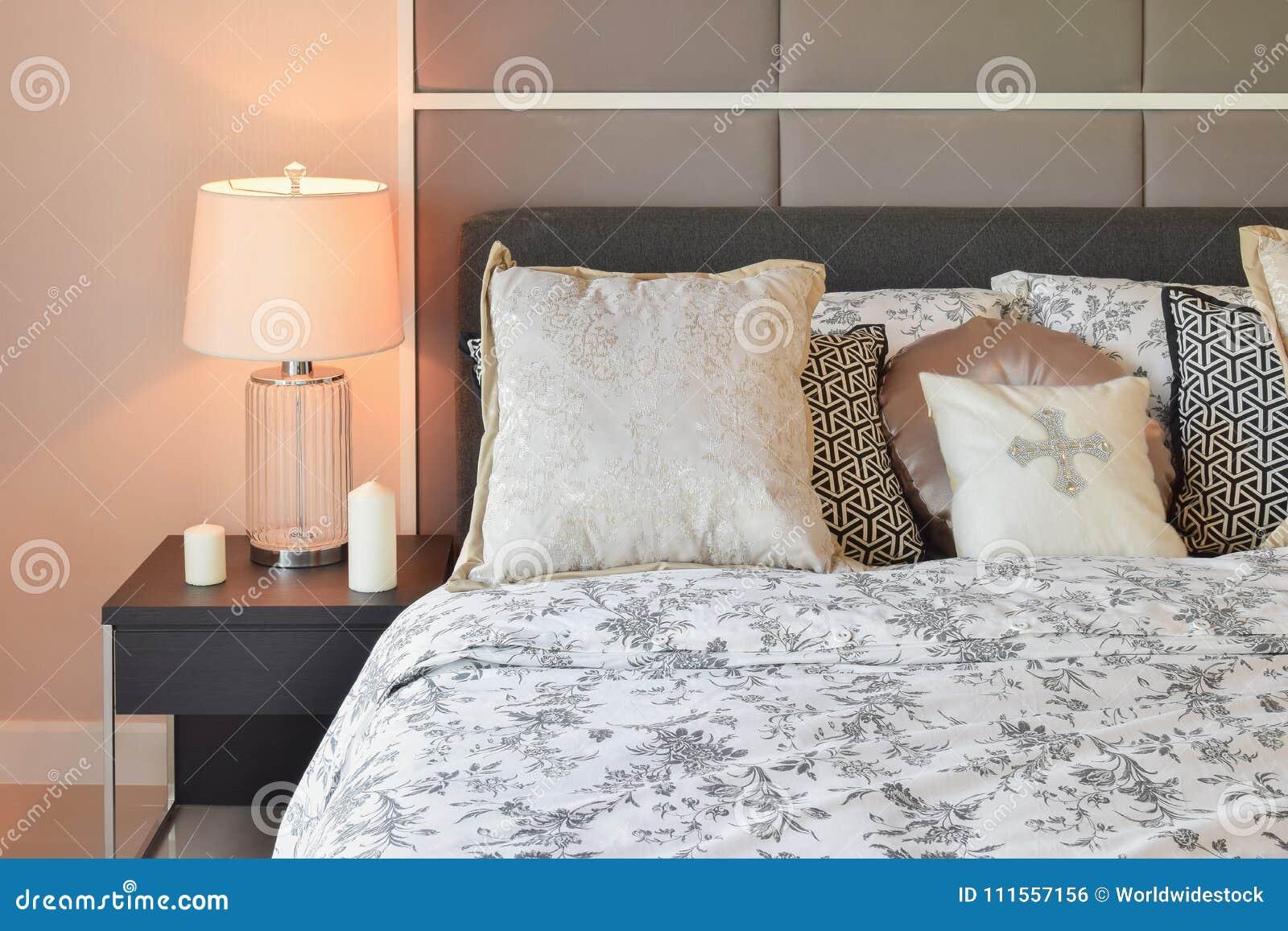 Dormitorio de lujo con las almohadas del estampado de plores y la lámpara de mesa decorativa