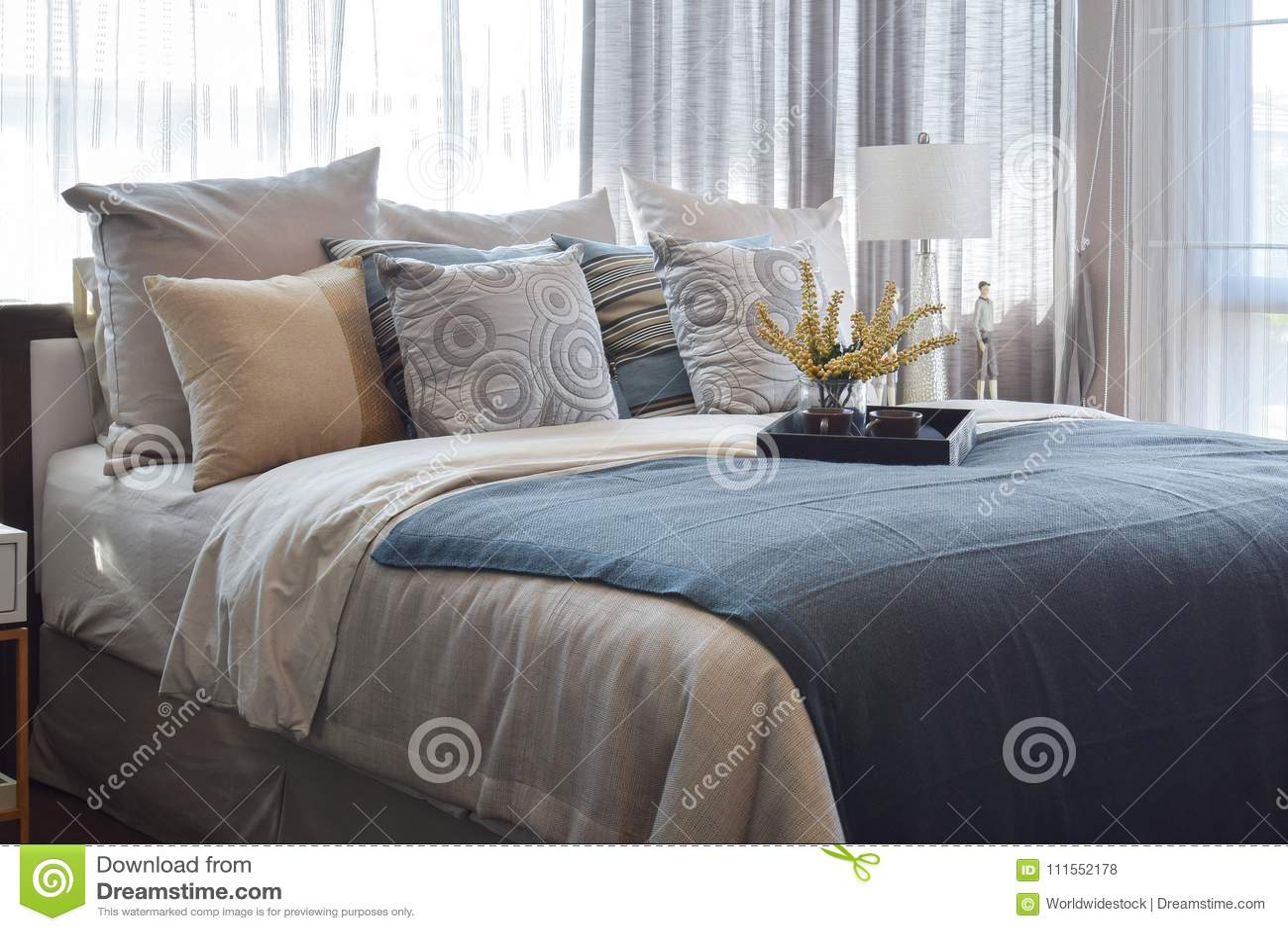 Dormitorio de lujo con las almohadas rayadas y juego de té decorativo en cama
