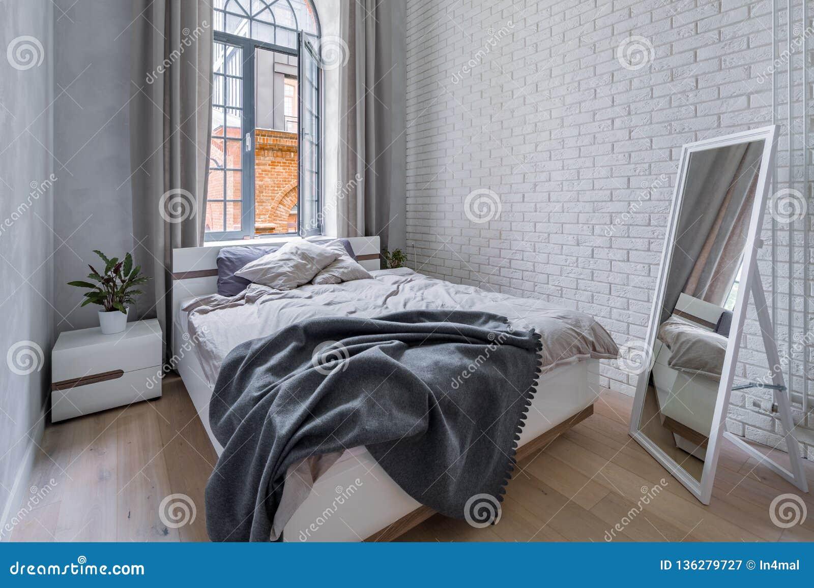 Dormitorio del desván con la pared de ladrillo