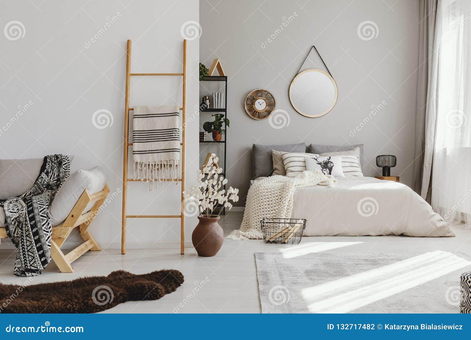 Dormitorio del espacio abierto interior con la ventana con las cortinas, el espejo y el reloj en la pared, escalera con la manta,