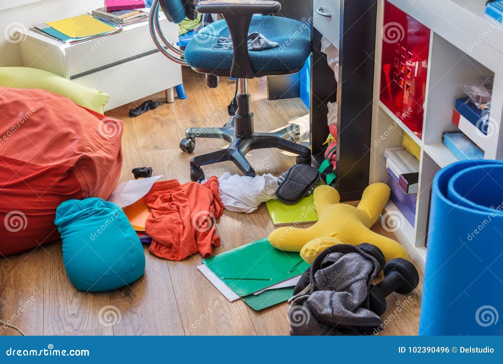 Dormitorio sucio del muchacho con ropa y almohadas en el piso