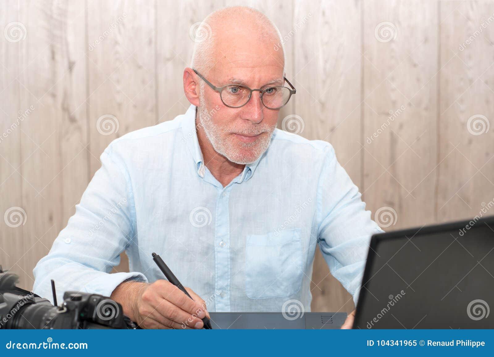 Dorośleć mężczyzna pracuje na jego grafiki pastylce