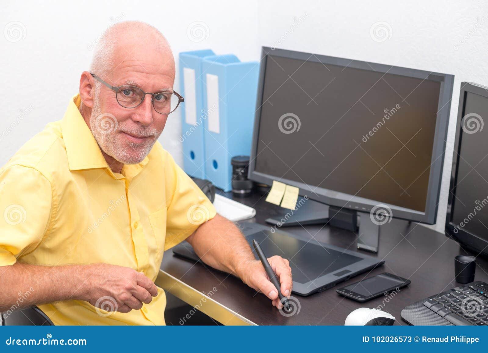 Dorośleć mężczyzna pracuje z grafiki pastylką w jego biurze