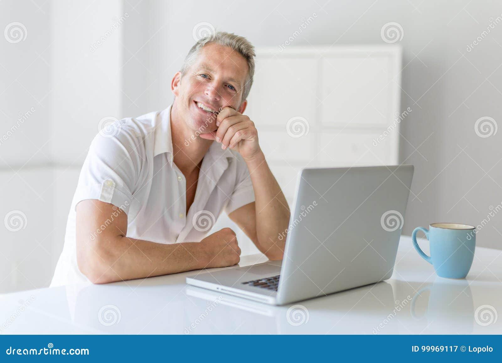 Dorośleć mężczyzna Używa laptop Na biurku W Domu