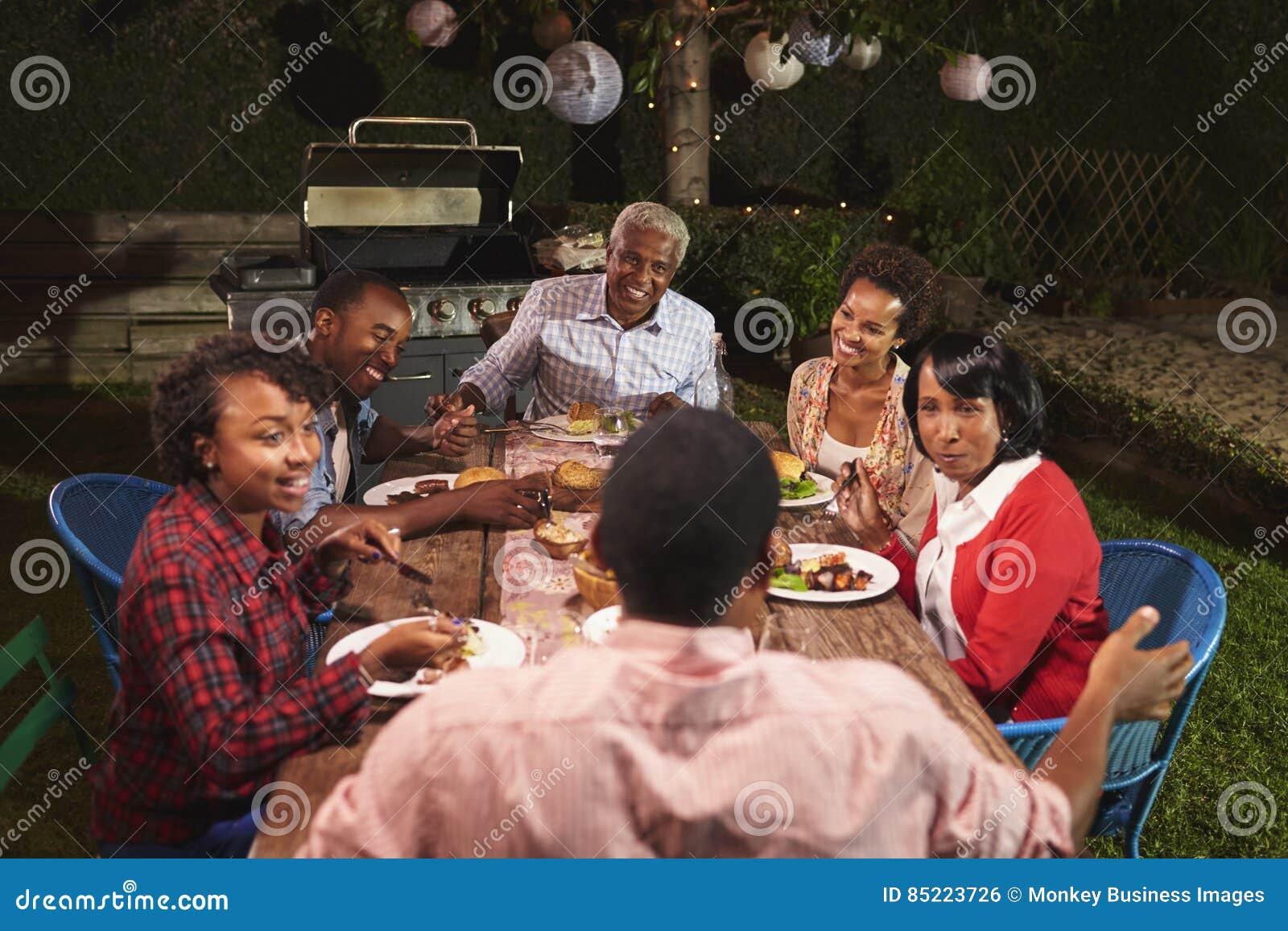 Dorosła czarna rodzina opowiada przy gościem restauracji w ich ogródzie