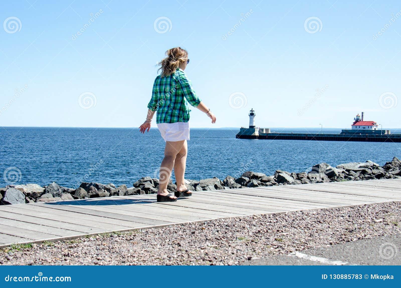 Dorosła kobieta bierze relaksującego przespacerowanie na Duluth kanału parku Lakewalk