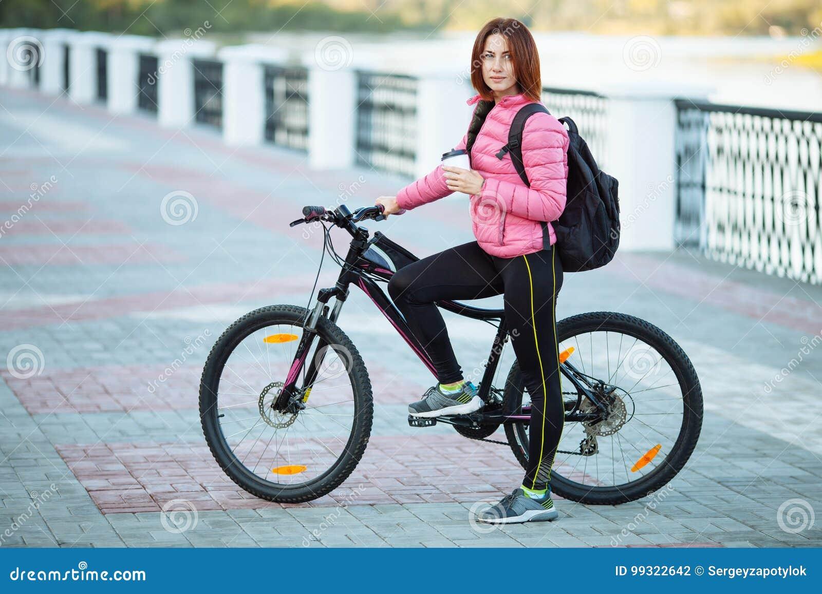 Dorosła piękna rudzielec kobieta pije ranek kawę pozuje na bicyklu w jesieni miasta rzeki molu z koczka ostrzyżenia główkowaniem