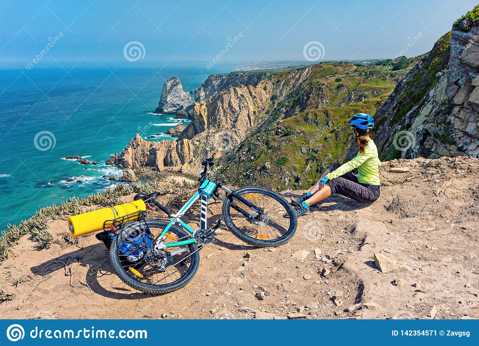 Dorosły atrakcyjny żeński cyklista z jej rowerem górskim siedzi na oceanu skalistym wybrzeżu