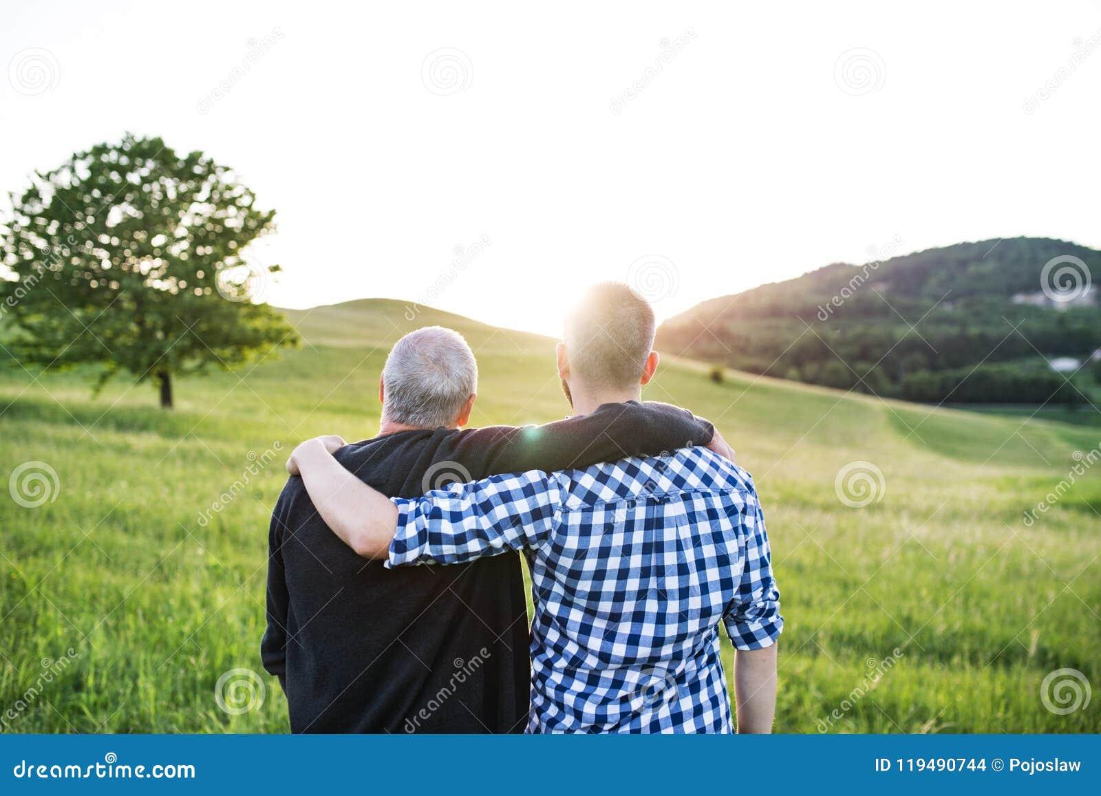 Dorosły modnisia syn z starszą ojciec pozycją w naturze przy zmierzchem odosobniony tylni widok biel