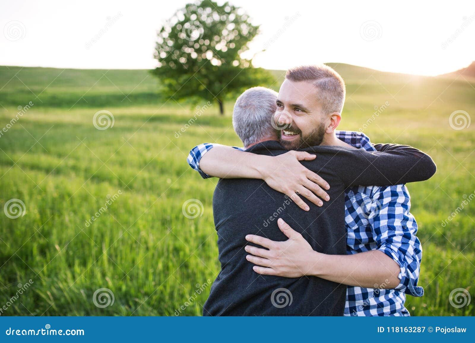 Dorosły modnisia syn z starszym ojcem na spacerze w naturze przy zmierzchem, ściska