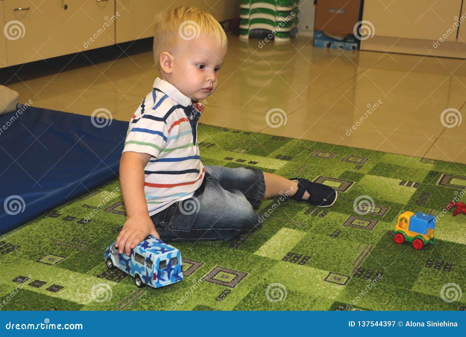 Dos años del niño de juego del muchacho con los coches Juguetes educativos para el preescolar y el niño de la guardería, patio in